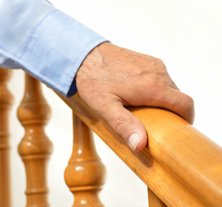 Hand gripping stairway banister